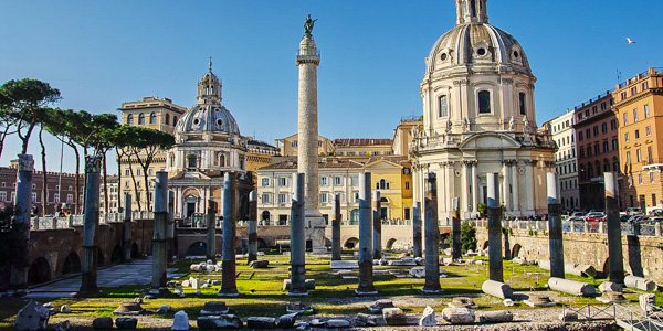 The columns of the Basilica Ulpia backed by Trajan's Column (and a pair of baroque church domes) in the Forum of Trajan, part of Rome's Imperial Fori