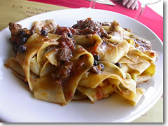 A heaping plate of Tuscany's famous pappardelle al chinghiale (sheet-like noodles with wild boar sauce).