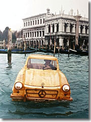 Artist Livio De Marchi driving his hand-made wooden Mecedes 300SL along teh Grand Canal past Piazza San Marco and into the Bacino San Marco.