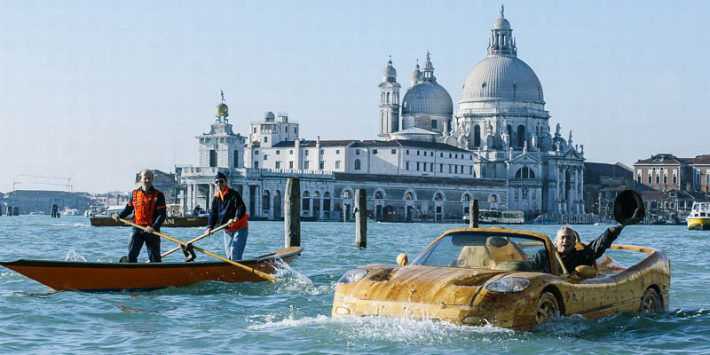 Artist Livio De Marchi driving his hand-made wooden Ferrari in the Bacino San Marco..