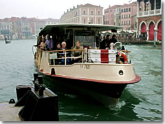 A vaporetto, the Venetian water bus or public ferry, arriving on the Grand Canal in Venice