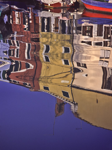 The houses of Burano, reflected here in one of its quiet fishing canals, are each painted in a different super-saturated color with fantastically mismatching colors on the shutters and trim.